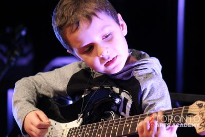 young boy playing guitar onstage