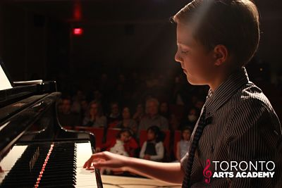 boy piano lesson student onstage performing piano