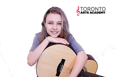 girl playing guitar in guitar lessons
