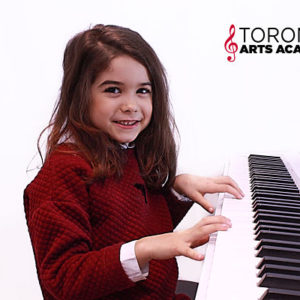 girl playing piano in piano lesson at our music school