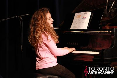 girl playing piano onstage_opt