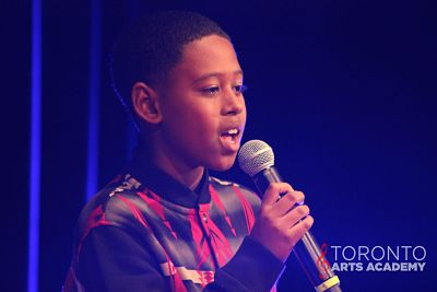 young-boy-singing-on-mic-onstage_voice_lessons