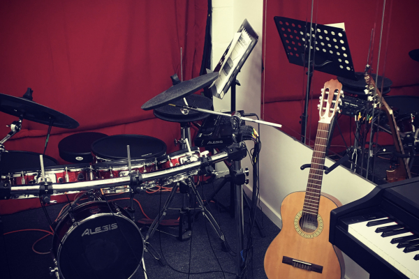drum lesson room with drum kit and guitar and red curtain_opt
