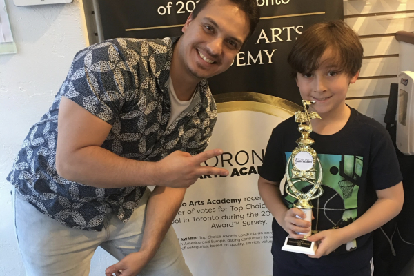 drum student recieving trophy for passing musical test_opt