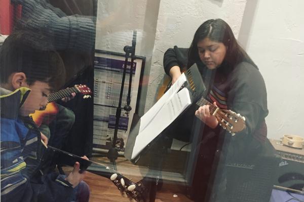 guitar teacher teaching guitar lesson student in guitar lesson room_opt