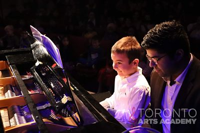 male piano teacher performing onstage with piano student_opt