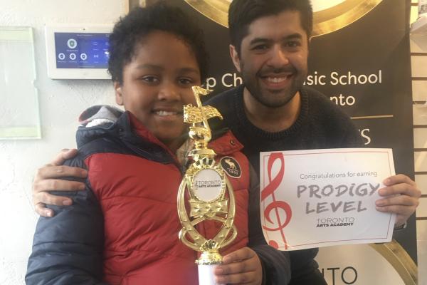 music student winning trophy with music teacher_opt