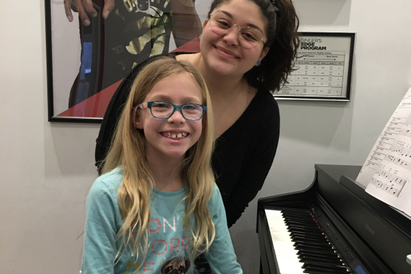 piano lesson student with piano teacher smiling for camera_opt