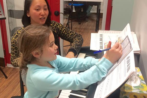 a toronto piano lesson with piano teacher and piano student writing in lesson book