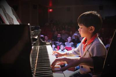 boy toronto piano lessons students plays onstage with teacher