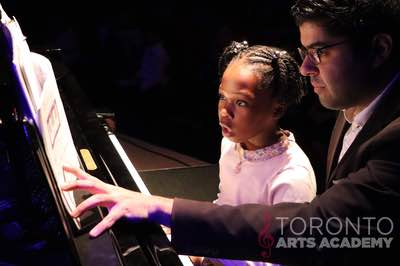 piano lesson student young girl ponytails onstage with piano teacher 400