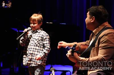 voice lesson student boy smiling onstage holding microphone with voice teacher playing guitar 400
