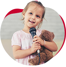 young girl holding teddy bear singing into mic motivational rewards