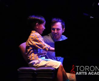 boy piano student with piano teacher sitting beside him on stage